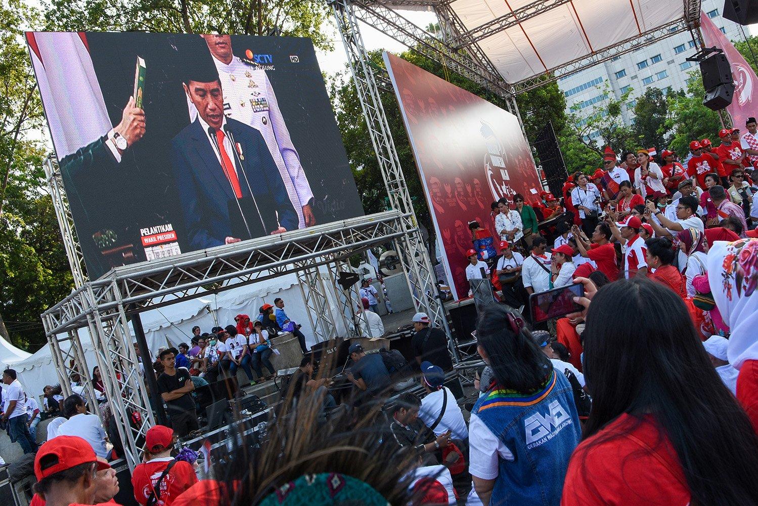 Sejumlah warga menonton bersama pelantikan Presiden dan Wakil Presiden terpilih periode 2019-2024 Joko Widodo - Ma\'ruf Amin melalui layar yang disediakan di Taman Aspirasi, Jakara, Minggu (20/10/2019).