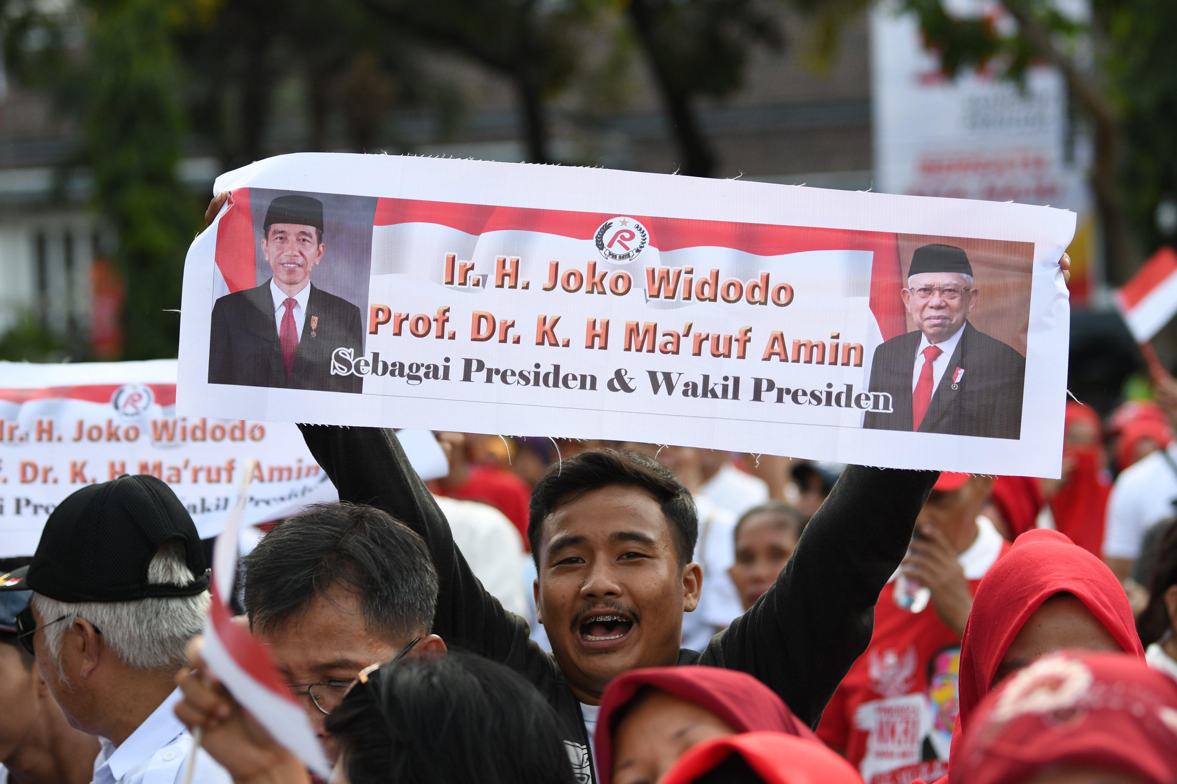 Seorang warga membawa poster bergambarkan Presiden Joko Widodo dan Wakil Presiden Ma\'ruf Amin saat Syukuran Inaugurasi Presiden dan Wakil Presiden 2019-2024 terpilih di Taman Aspirasi, Jakarta, Minggu (20/10/2019).