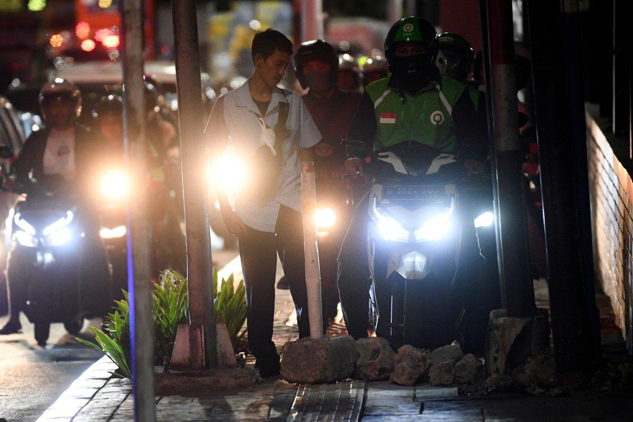 Seorang karyawan swasta, Arif menghalau sepeda motor yang menaiki trotoar dengan memasang batu di Jalan Menteng Raya, Jakarta, Senin (18/11/2019). Aksi tersebut dilakukan karena masih banyak pengendara sepeda motor menaiki trotoar yang dikhususkan untuk pejalan kaki untuk menghindari macet.