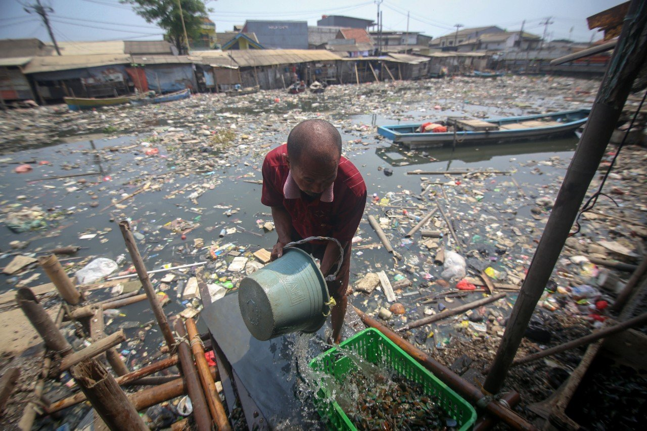 Seorang warga mengambil air untuk membersihkan kerang dagangannya di Kali Apuran yang tercemar limbah di Dadap, Kabupaten Tangerang, Banten, Rabu (20/11/2019). Kondisi air Kali Apuran berubah warna menjadi hitam dan mengeluarkan bau serta dipenuhi sampah akibat pembuangan limbah rumah tangga oleh masyarakat yang berada di sekitar daerah tersebut. \r\n