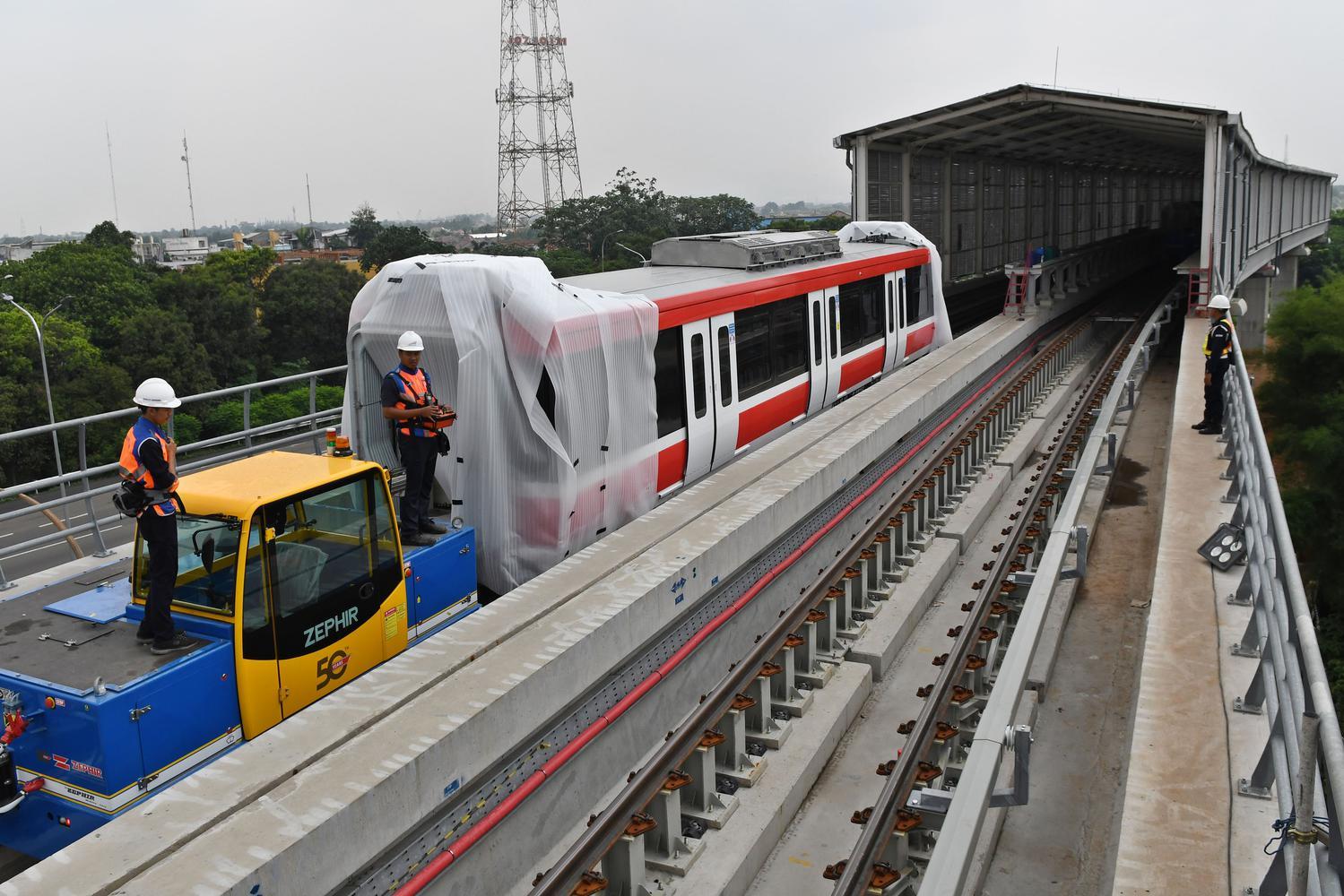 Sejumlah petugas mengoperasikan alat pendorong gerbong kereta 'light rail train' atau lintas rel terpadu (LRT) yang telah diangkat ke atas rel di Stasiun Harjamukti, Cimanggis, Kota Depok, Jawa Barat, Rabu (4/12/2019).