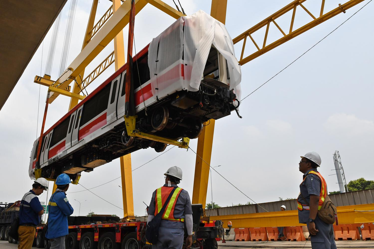 Sejumlah petugas mengawasi proses pengangkatan gerbong kereta 'light rail train' atau lintas rel terpadu (LRT) ke atas rel di Stasiun Harjamukti, Cimanggis, Kota Depok, Jawa Barat, Rabu (4/12/2019).