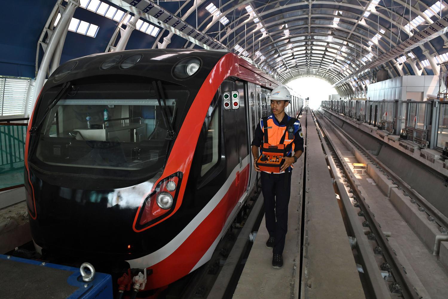 Petugas melintasi gerbong kereta 'light rail train' atau lintas rel terpadu (LRT) di Stasiun Harjamukti, Cimanggis, Kota Depok, Jawa Barat, Rabu (4/12/2019). LRT Jabodebek koridor Cibubur-Dukuh Atas mempunyai kapasitas sebanyak 250 orang per gerbong