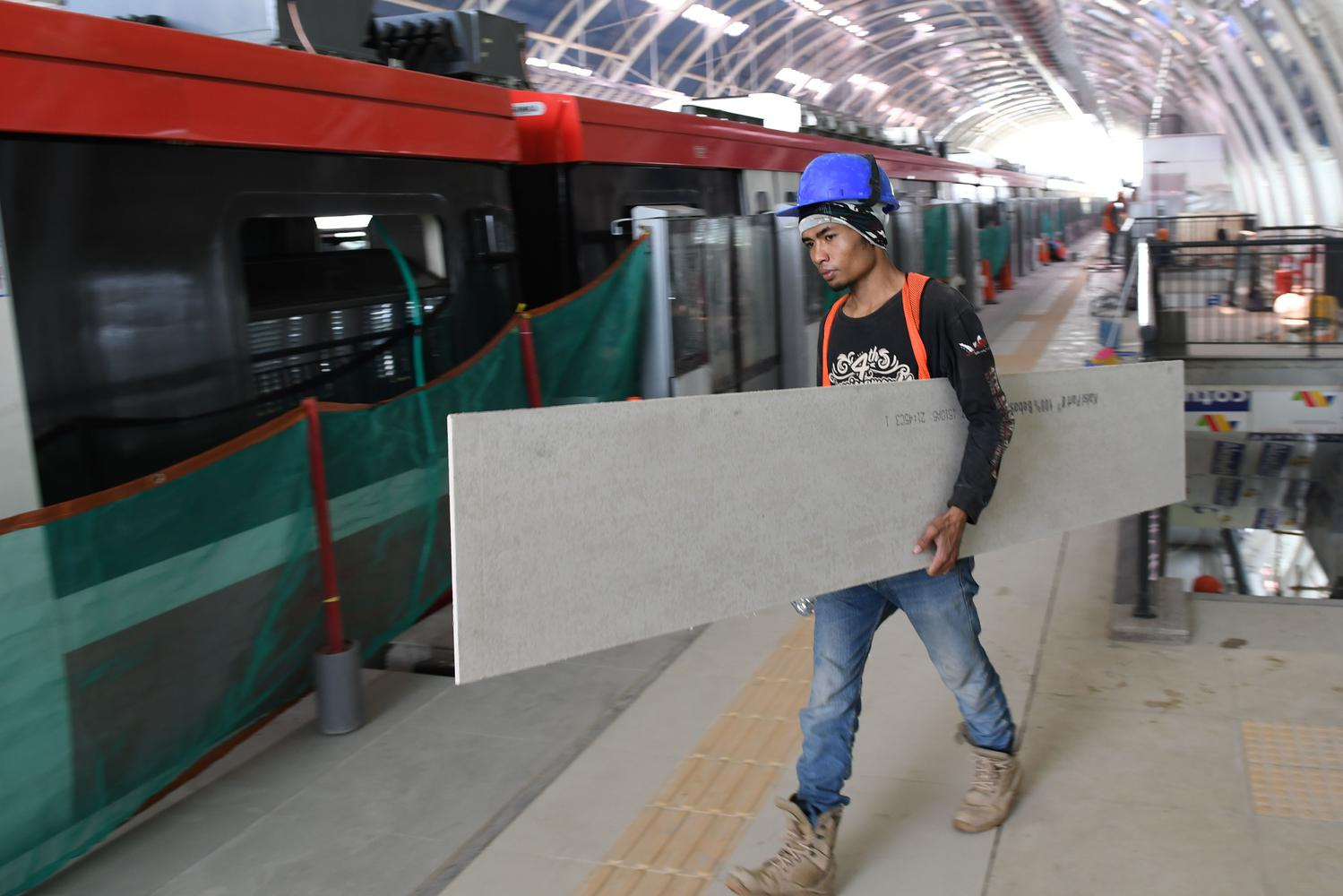 Pekerja melintasi gerbong kereta 'light rail train' atau lintas rel terpadu (LRT) di Stasiun Harjamukti, Cimanggis, Kota Depok, Jawa Barat, Rabu (4/12/2019).