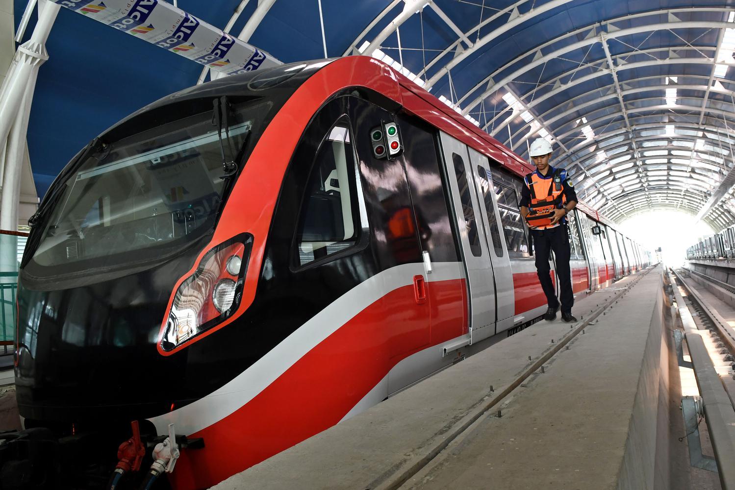 Petugas melintasi gerbong kereta 'light rail train' atau lintas rel terpadu (LRT) di Stasiun Harjamukti, Cimanggis, Kota Depok, Jawa Barat, Rabu (4/12/2019). Pemerintah menargetkan LRT Jabodebek koridor Cibubur-Dukuh Atas dapat beroperasi pada 2021