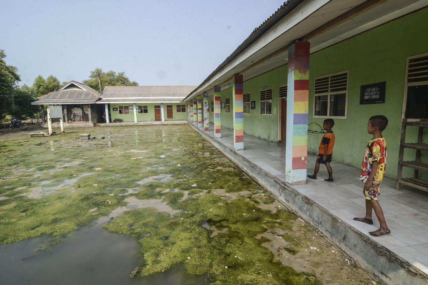 Dua bocah bermain di halaman sekolah yang tergenang banjir rob di Desa Pantai Bahagia, Muaragembong, Kabupaten Bekasi, Jawa Barat, Selasa (6/8/2019). Banjir rob menggenangi sejumlah fasilitas umum yang berada di Desa Bahagia akibat letaknya yang lebih rendah dari permukaan laut.