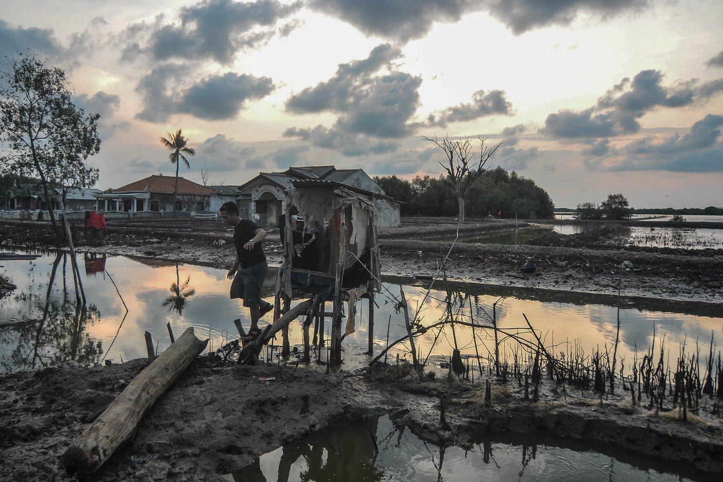 Seorang warga keluar dari sarana MCK di Kampung Beting, Desa Pantai Bahagia, Kecamatan Muara Gembong, Kabupaten Bekasi, Jawa Barat, Selasa (26/11/2019).