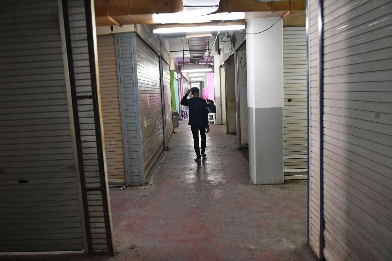 Warga melintasi kios-kios kosong yang disiapkan sebagai lokasi relokasi pedagang kaki lima (PKL) pakaian bekas Pasar Senen di lantai dua Pasar Kenari, Jakarta, Senin (2/12/2019). Para pedagang pakaian bekas Pasar Senen menolak dipindah ke Pasar Kenari karena khawatir sepi pembeli di lokasi yang baru. \r\n