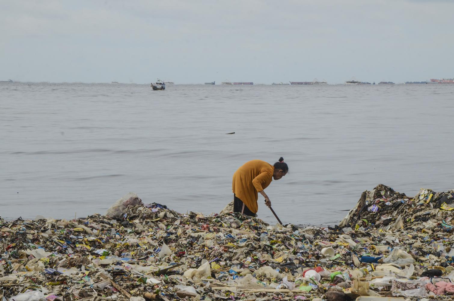 Warga beraktivitas di sekitar tumpukan sampah Pesisir laut Cilincing, Jakarta Utara, Selasa (10/12/2019). Sampah plastik yang menumpuk di sekitar pesisir laut Cilincing membahayakan kehidupan Biota Laut dan warga sekitar.