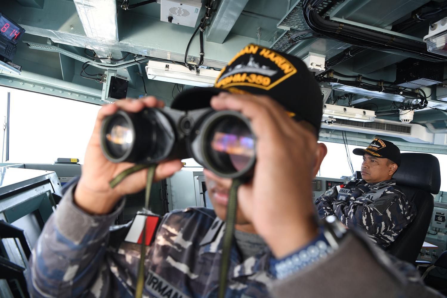 Komadan KRI Usman Harun Kolonel Laut (P) Himawan (kanan) mengamati monitor di anjungan KRI Usman Harun-359 ketika memasuki perairan Timor Leste di Dili, Timor Leste, Rabu (11/12/2019).