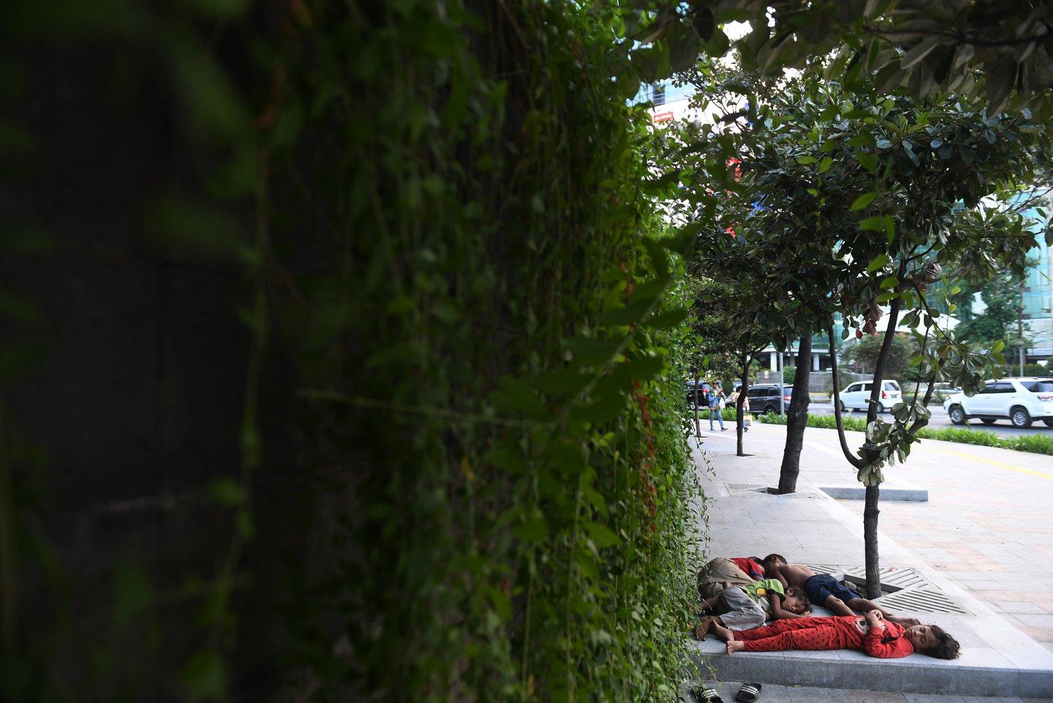 Sejumlah anak tertidur di trotoar kawasan Bundaran HI, Jakarta, Minggu (8/12/2019). Anak-anak yang tumbuh besar di jalanan tanpa pengawasan rentan terseret ke dunia kriminalitas hingga menjadi korban kekerasan fisik maupun seksual.