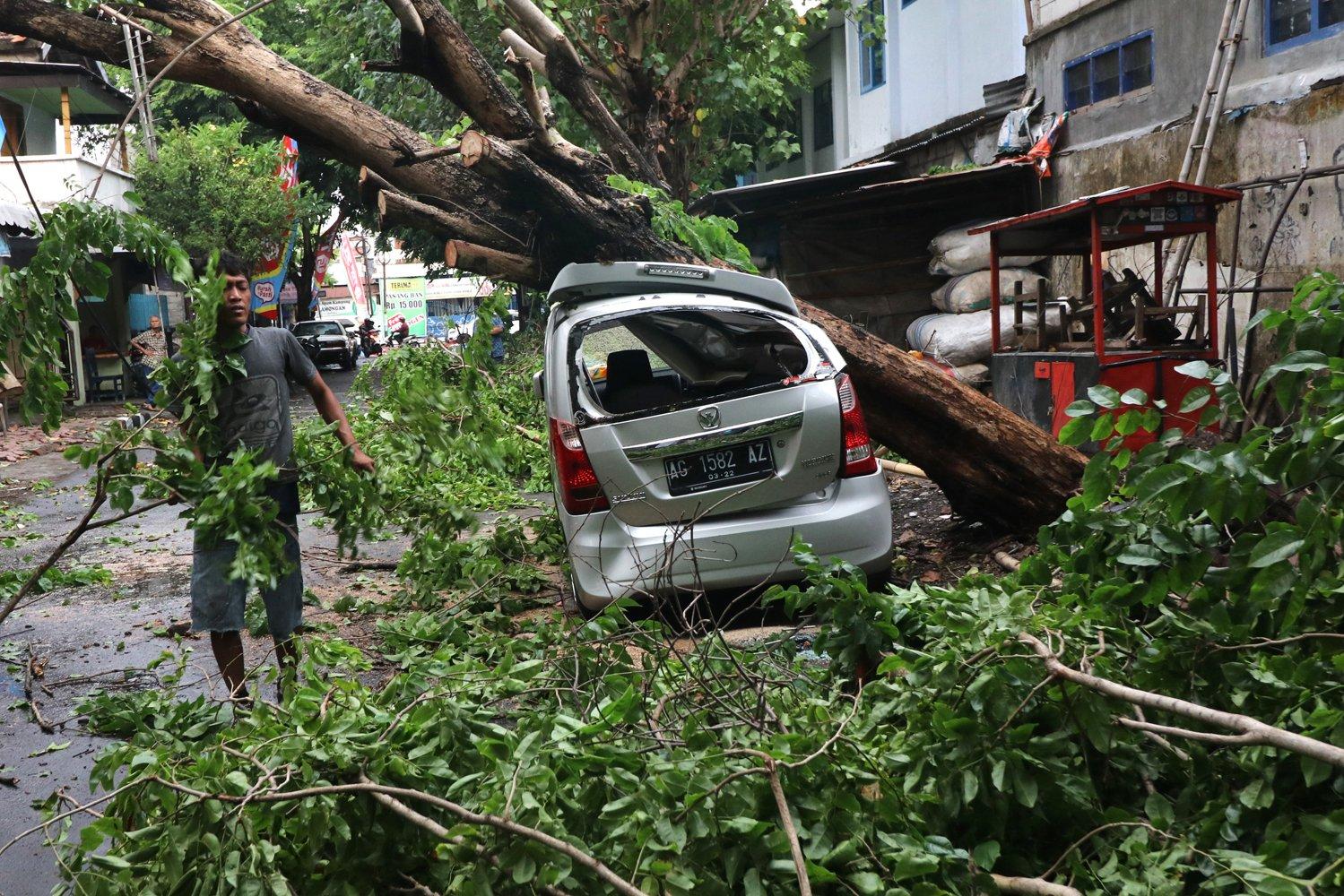 Warga memotong pohon yang menimpa sebuah mobil pascabencana angin kencang di Kota Kediri, Jawa Timur, Senin (9/12/2019). Bencana angin kencang yang disertai hujan lebat di daerah tersebut mengakibatkan satu orang meninggal dunia, tiga mobil rusak dan sejumlah bangunan roboh.