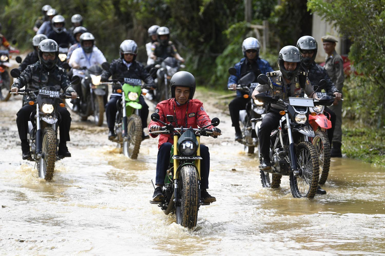 Presiden Joko Widodo (tengah) mengendarai motor Copper menerjang genangan air saat kunjungan kerja di Kecamatan Krayan, Kabupaten Nunukan, Kalimantan Utara, Kamis (19/12/2019).