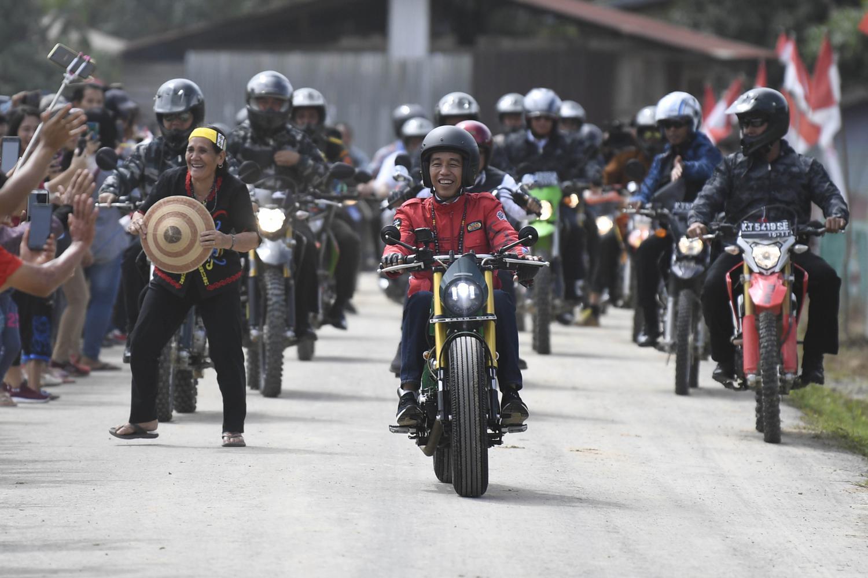 Warga mengabadikan momen Jokowi, yang terlihat mengenakan jaket berwarna merah buatan Bulls Syndicate saat riding motornya yang berwarna hijau. Sejumlah Paspampres dengan motor trail pun mengikuti di belakang Presiden.
