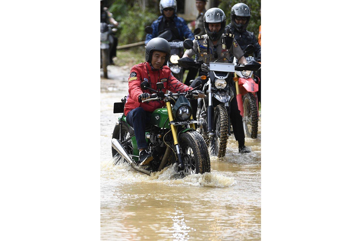 Jokowi terlihat mengenakan helm berwarna hitam lengkap dan sarung tangan berwarna hitam. Jalan tanah hingga genangan air di lalui Jokowi dan rombongannya.