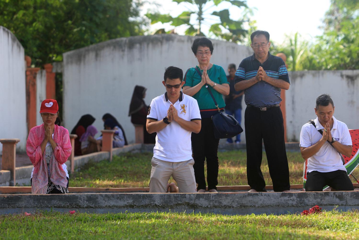 Sejumlah umat muslim bersama warga keturunan Tionghua melaksanakan doa bersama saat berziarah ke kuburan massal korban gempa dan gelombang tsunami di Desa Suak Indrapuri, Johan Pahlawan, Aceh Barat, Aceh, Kamis (26/12/2019).