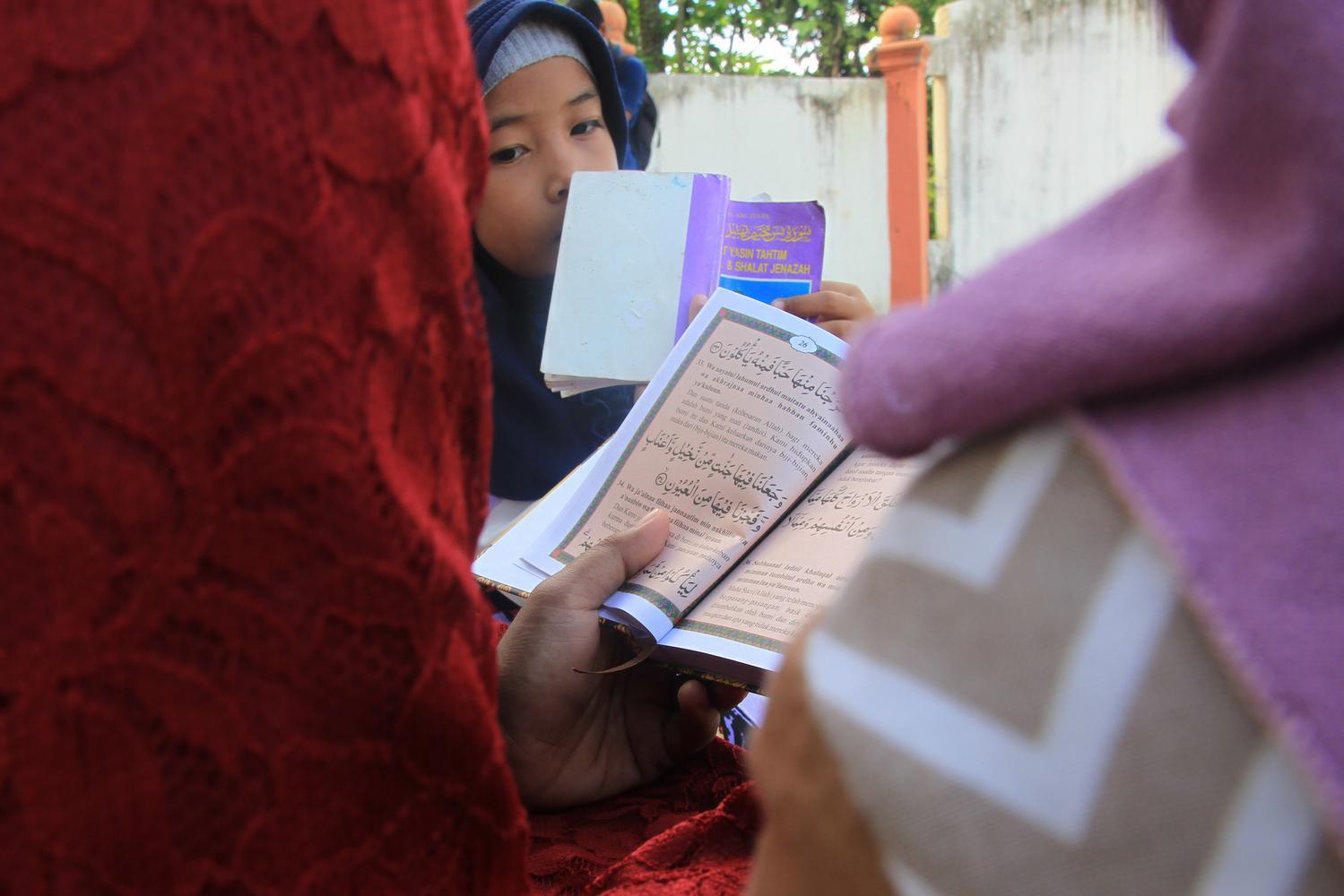 Sejumlah umat muslim membaca Surat Yasin dan doa bersama saat berziarah ke kuburan massal korban gempa dan gelombang tsunami di Desa Suak Indrapuri, Johan Pahlawan, Aceh Barat, Aceh, Kamis (26/12/2019).