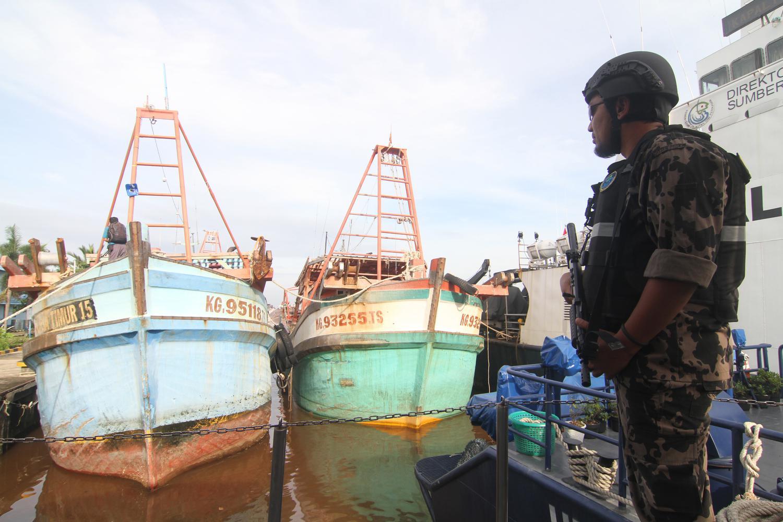 Seorang petugas Kapal Pengawas Kementerian Kelautan dan Perikanan bersiaga di sekitar kapal pencuri ikan berbendera Vietnam hasil tangkapan di Stasiun Pengawasan Sumber Daya Kelautan dan Perikanan (PSDKP) Pontianak di Sungai Rengas, Kabupaten Kubu Raya, Kalimantan Barat, Kamis (9/1/2020).