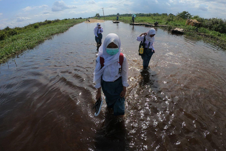 Sejumlah pelajar melewati jalan penghubung Desa Jebus dengan Desa Gedong Karya yang terendam banjir luapan Sungai Batanghari di Muarojambi, Jambi, Selasa (7/1/2020). Ruas jalan penghubung desa satu-satunya tersebut terendam banjir sejak dua pekan terakhir.