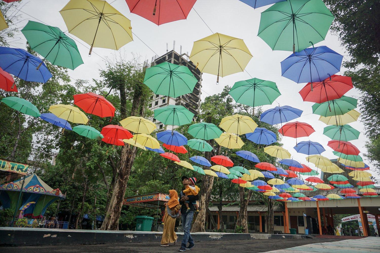 Pengunjung melintas di bawah deretan payung hias di Taman Satwa Taru Jurug (TSTJ), Solo, Jawa Tengah, Rabu (8/1/2020). Deretan payung hias dengan konsep menyambut musim hujan tersebut untuk mempercantik serta meningkatkan daya tarik kunjungan wisata ke Kebun Binatang TSTJ.