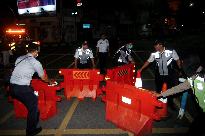 Petugas melakukan pengalihan jalur saat penutupan sebagian jalan protokol Kota Tegal, Jawa Tengah, Senin (22/3/2020) malam. Pemerintah Kota Tegal dan Polres Tegal hingga 14 hari mendatang melakukan