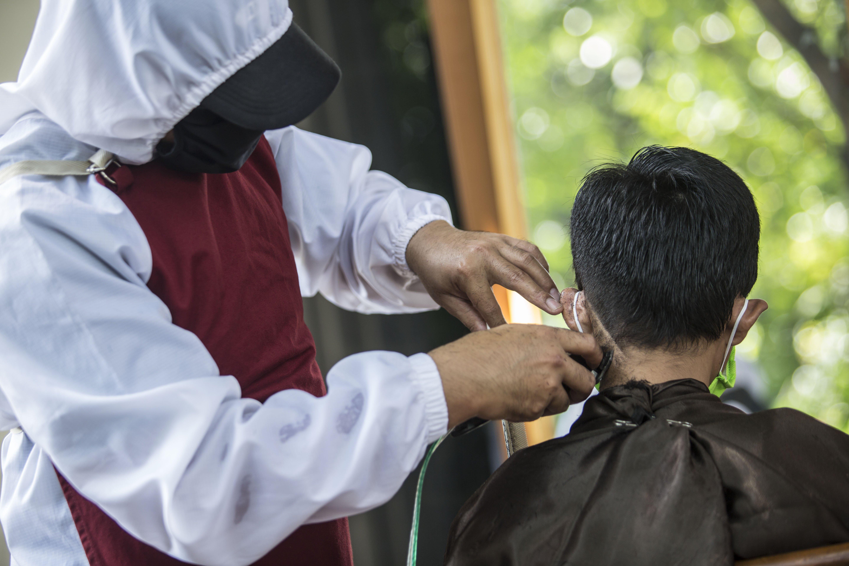 Tukang cukur menggunakan Alat Pelindung Diri (APD) saat memotong rambut di halaman rumah pelanggan di Gang Poncol, Cimanggis, Kota Depok, Rabu (29/4/2020). Penerapan Pembatasan Sosial Berskala Besar (PSBB) Kota Depok membuat pelaku usaha cukur rambut tersebut menerima jasa panggilan ke rumah dengan menggunakan APD sebagai upaya pencegahan virus korona (Covid-19).