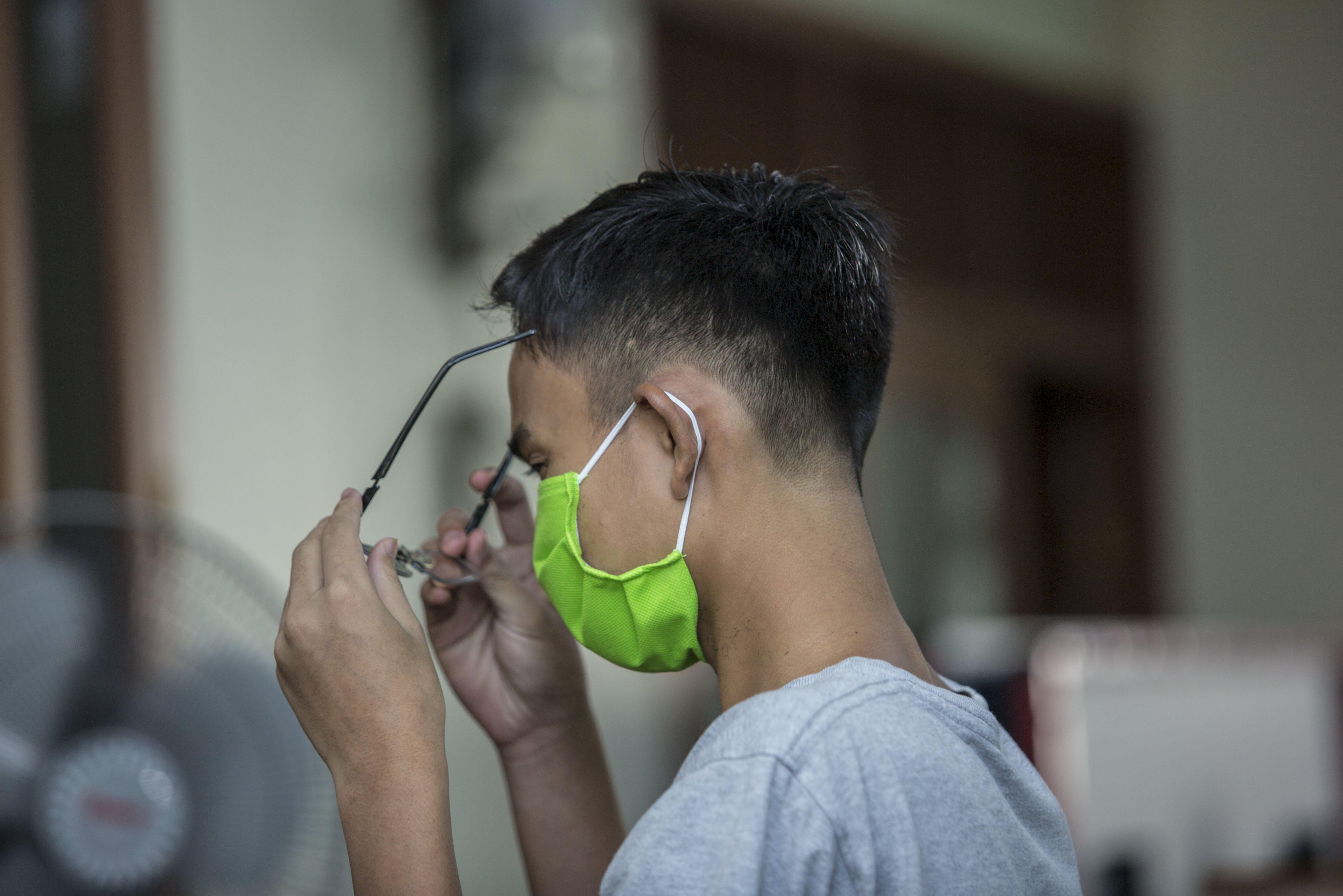 Pelanggan menggunakan kaca mata setelah selesai di cukur mengunakan jasa cukur rambut pangilan di Gang Poncol, Cimanggis, Kota Depok, Rabu (29/4/2020). Penerapan Pembatasan Sosial Berskala Besar (PSBB) Kota Depok membuat pelaku usaha cukur rambut tersebut menerima jasa panggilan ke rumah dengan menggunakan APD sebagai upaya pencegahan virus korona (Covid-19).