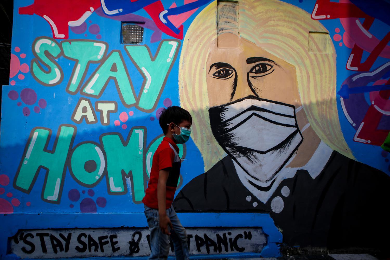 Seorang warga melintas di depan mural tentang COVID-19 di Kampung Pinkli, Kota Tangerang, Banten, Senin (11/5/2020). Mural tersebut ditujukkan kepada masyarakat untuk tetap di rumah guna memutus rantai penyebaran COVID-19.