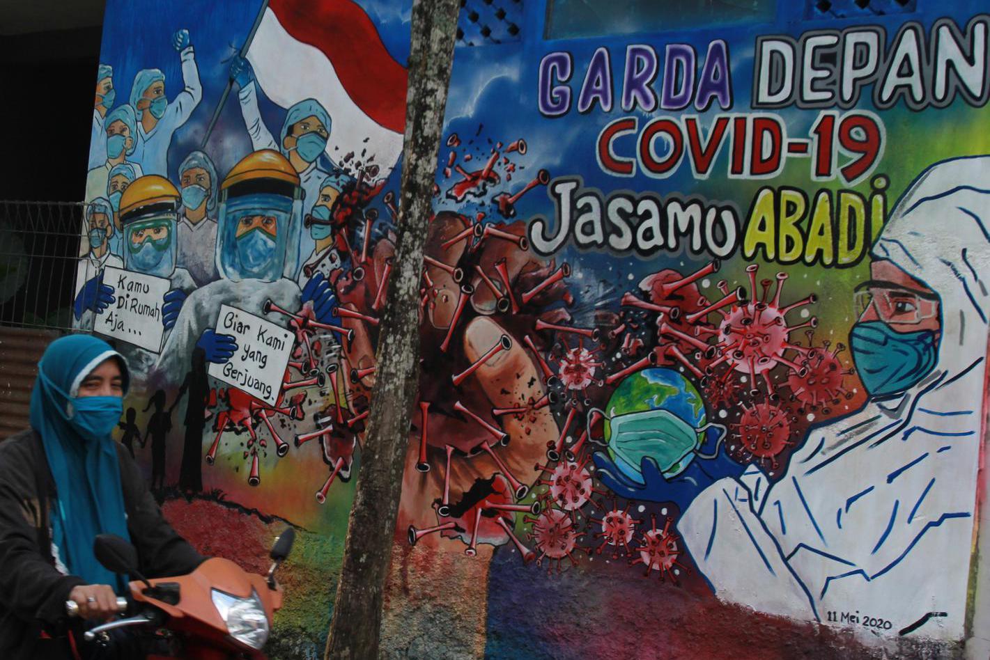 Pengendara motor melintas di depan mural yang bergambar dukungan untuk tenaga medis yang ada di Kavling Kinayung Pondok Aren, Tangerang Selatan, Banten, Jumat (15/5/2020). Mural yang dibuat oleh warga itu bertujuan untuk memberikan dukungan dan apresiasi atas perjuangan tenaga medis yang menjadi garis terdepan dalam penanganan COVID-19.
