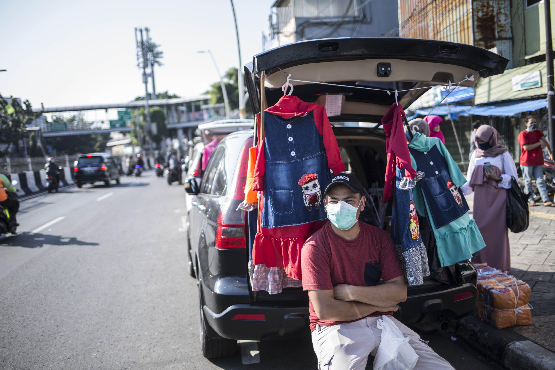 Pedagang menggelar lapak dagangannya menggunakan mobil pribadi di Jalan Matraman Raya, Jatinegara, Jakarta Timur, Rabu (220/5/2020). Puluhan mobil tersebut berjajar di pinggir jalan seakan membentuk pasar baru dengan mobil pribadi sebagai kios mereka. Pedagang mengatakan kalau ini bersifat darurat demi terpenuhinya kebutuhan sehari-hari selama masa pembatasan sosial berskala besar (PSBB).