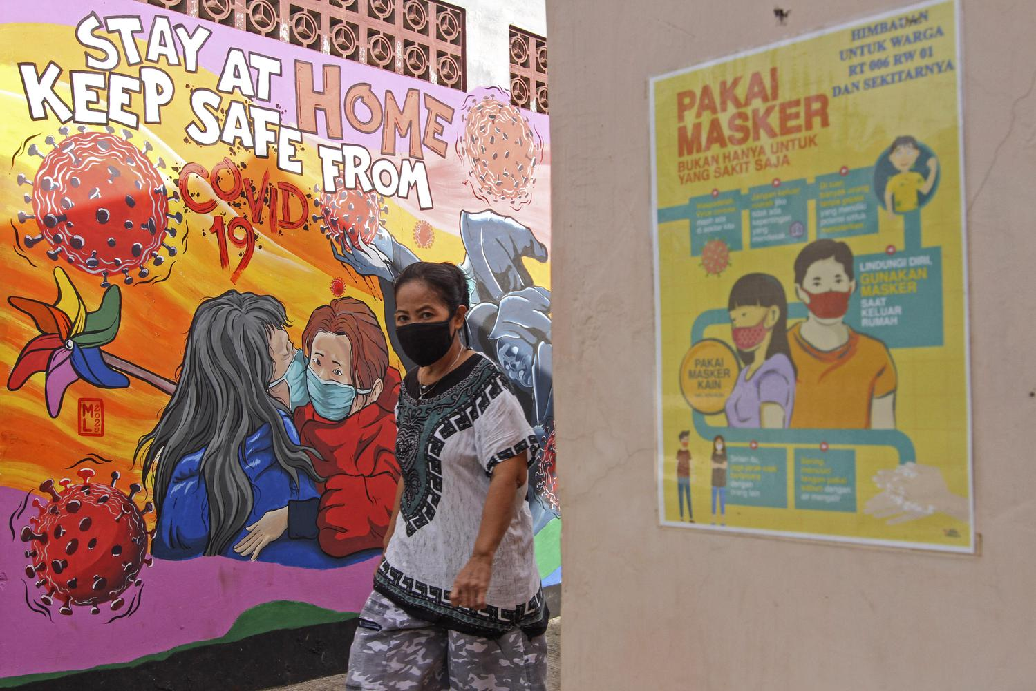 Seorang warga melintas di depan mural tentang COVID-19 di Pangkalan Jati Baru, Depok, Jawa Barat, Selasa (26/5/2020). Pembatasan Sosial Berskala Besar (PSBB) wilayah Kota dan Kabupaten Bogor, Depok, Kota dan Kabupaten Bekasi (Bodebek) untuk sementara diperpanjang hingga Jumat (29/5/2020) menyelaraskan diri dengan periode PSBB Jawa Barat.