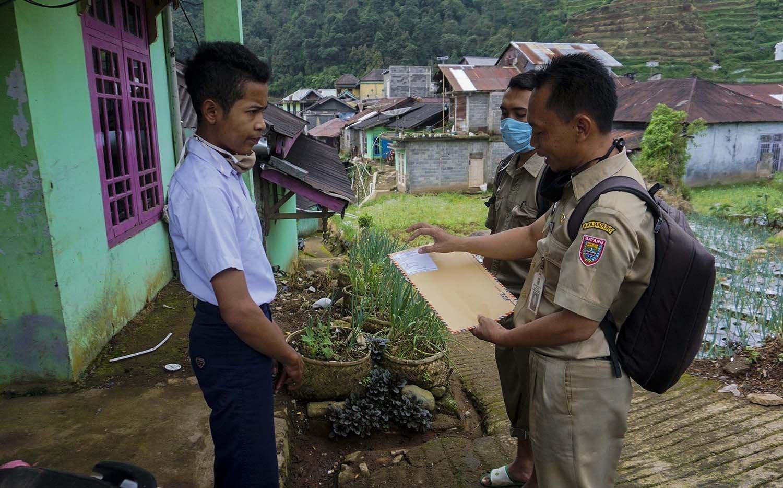 Kepala Sekolah SMP N 4 Bawang Mulud Sugito (kanan) dan guru Wiyata Bhakti menyerahkan berkas lembar tugas kepada siswa Khoerul Risal di rumahnya di Pranten, Kecamatan Bawang, Kabupaten Batang, Jawa Tengah.