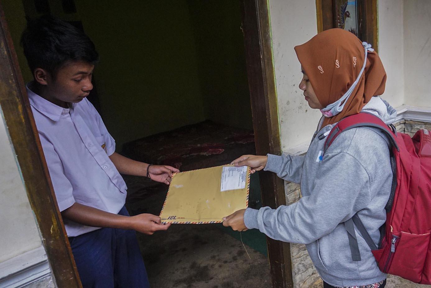 Siswa SMP N 4 Bawang, Dani Difanudin, menyerahkan lembar tugas sekolah kepada gurunya saat jemput bola di rumahnya di Pranten, Kecamatan Bawang, Kabupaten Batang, Jawa Tengah.\r\n\r\n