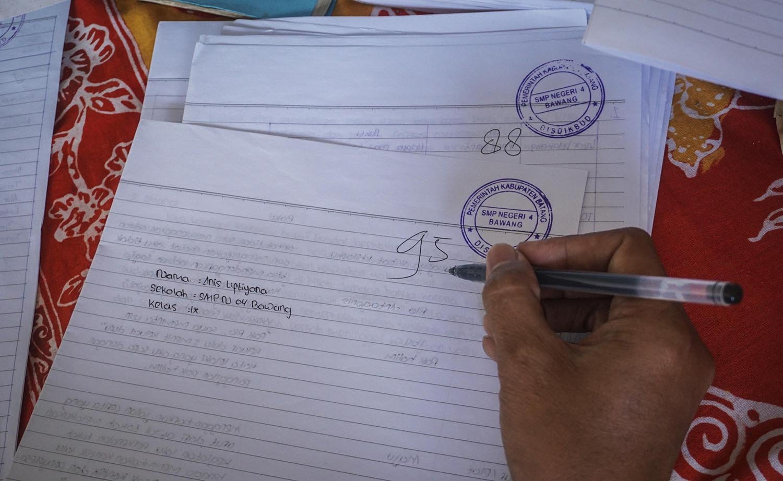 Kepala Sekolah SMP N 4 Bawang Mulud Sugito mengoreksi tugas sekolah siswa di SMP N 4 Bawang di Pranten, Kecamatan Bawang, Kabupaten Batang, Jawa Tengah.