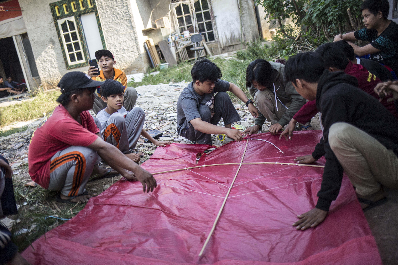 Jaya (17) bersama kawan-kawannya menyelesaikan pembuatan layang-layang di Kawasan Gandaria, Depok, Jawa Barat, (1/7/2020). Ditengah libur sekolah akibat pendemi, sejumlah anak-anak di kawasan Gandaria mengisi waktu luang dengan membuat layang-layang berbentuk pesawat, kuntilanak dan pocong.