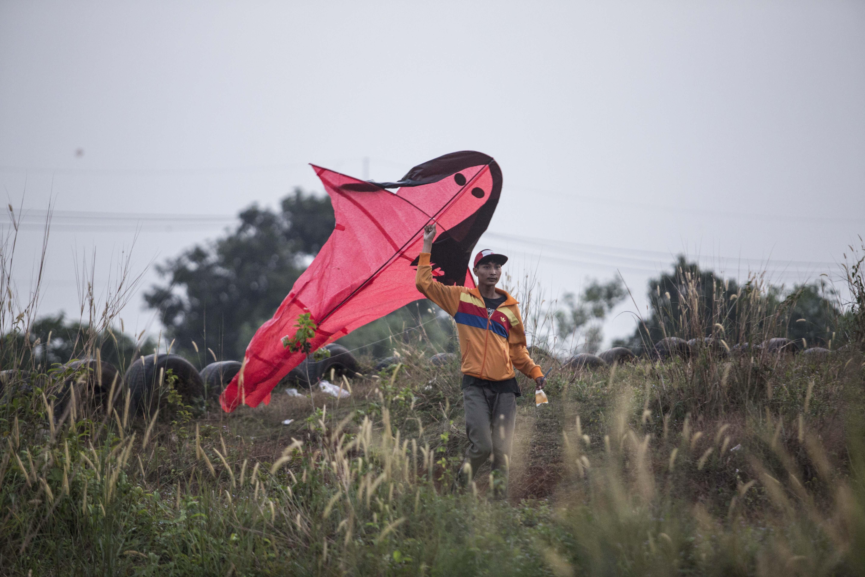 Jaya (17) bersama kawan-kawannya bersiap menerbangkan layang-layang di Kawasan Gandaria, Depok, Jawa Barat, (1/7/2020). Ditengah libur sekolah akibat pendemi, sejumlah anak-anak di kawasan Gandaria mengisi waktu luang dengan membuat layang-layang berbentuk pesawat, kuntilanak dan pocong.
