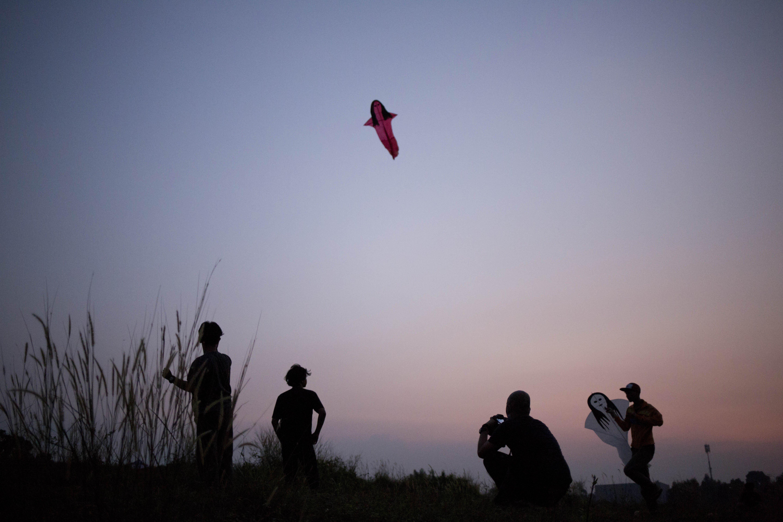 Jaya (17) bersama kawan-kawannya menerbangkan layang-layang di Kawasan Gandaria, Depok, Jawa Barat, (1/7/2020). Ditengah libur sekolah akibat pendemi, sejumlah anak-anak di kawasan Gandaria mengisi waktu luang dengan membuat layang-layang berbentuk pesawat, kuntilanak dan pocong.