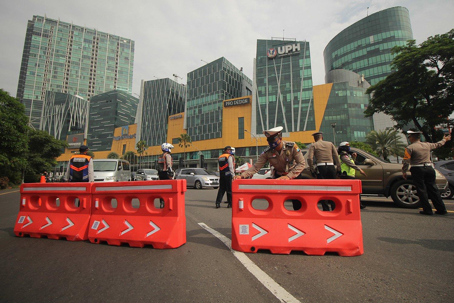 Polisi memasang \'water barrier\' saat pelaksanaan Pembatasan Sosial Berskala Besar (PSBB) di Surabaya di Bundaran Waru, Surabaya, Jawa Timur.