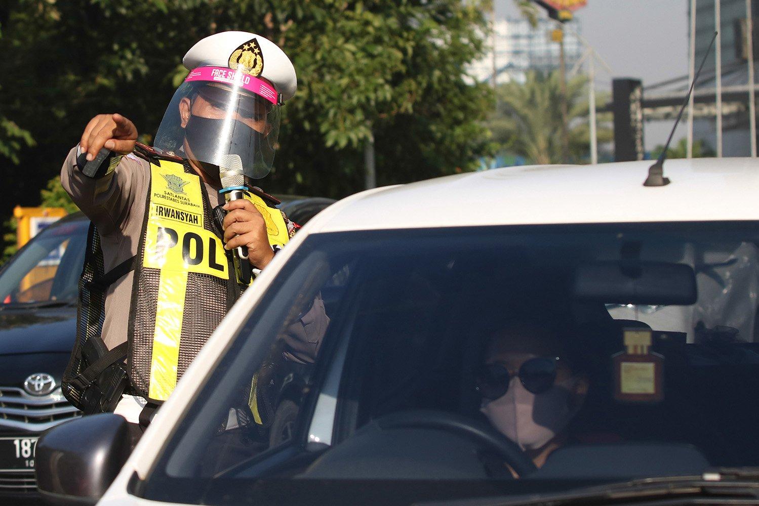 Polisi dengan menggunakan alat pelindung wajah melakukan penyekatan saat Pembatasan Sosial Berskala Besar (PSBB) Tahap III di Bundaran Waru, Surabaya, Jawa Timur.