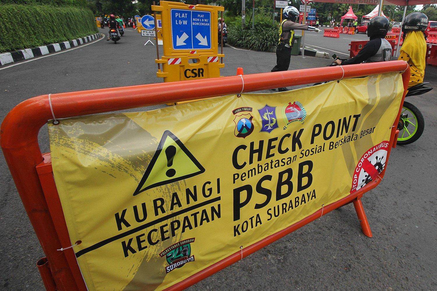 Polisi melakukan penyekatan di pos pemeriksaan Bundaran Waru, Surabaya, Jawa Timur.