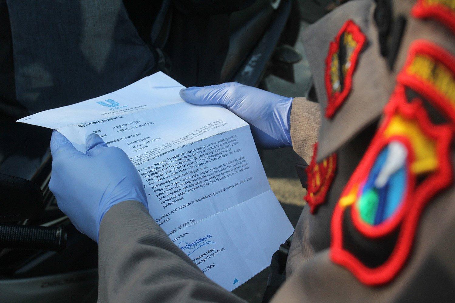 Polisi memeriksa dokumen perjalanan warga saat melakukan penyekatan Pembatasan Sosial Berskala Besar (PSBB) di Bundaran Waru, Surabaya, Jawa Timur.