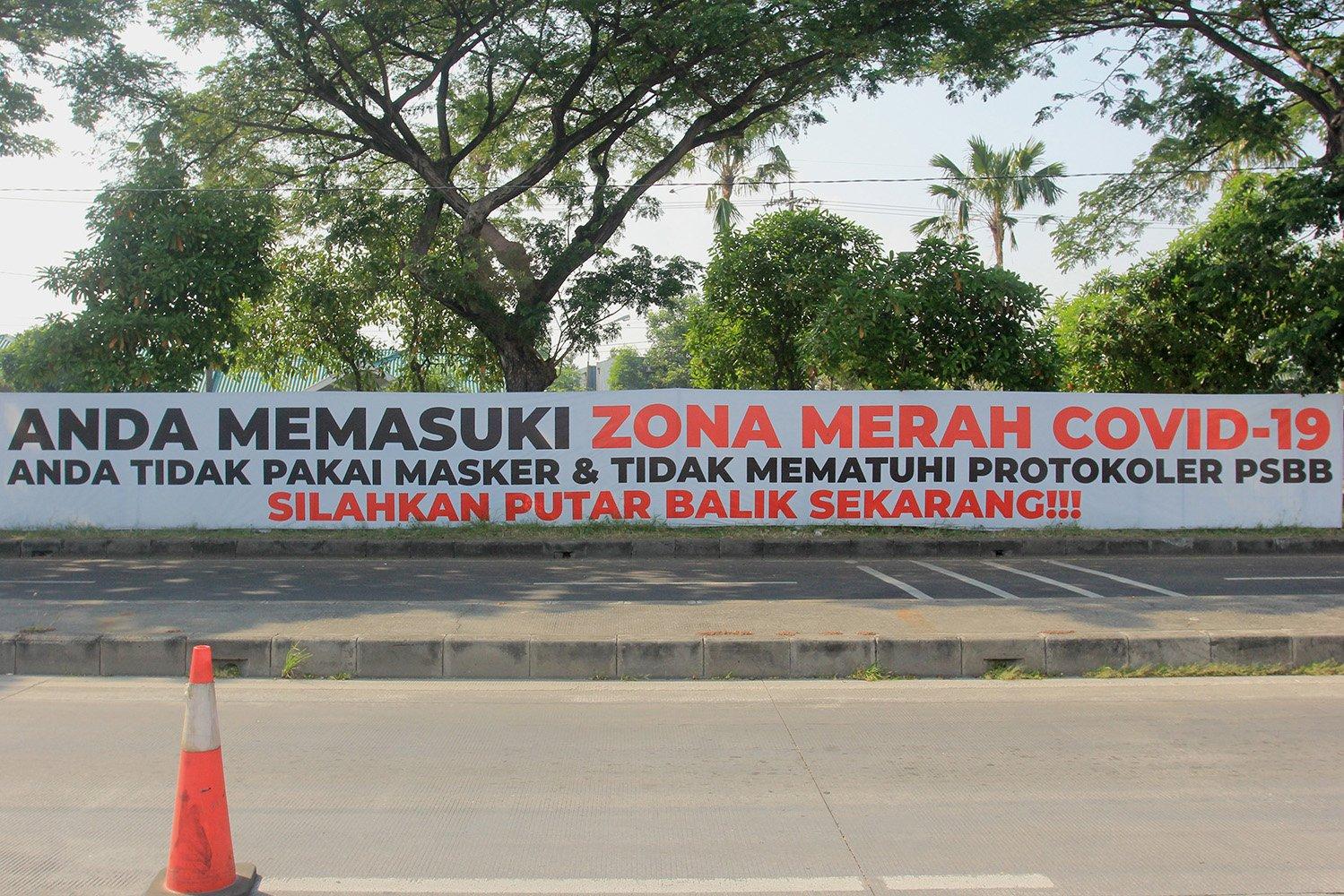 Sebuah spanduk bernada peringatan terpasang di pagar jalan di akses keluar Jembatan Suramadu, Surabaya, Jawa Timur.