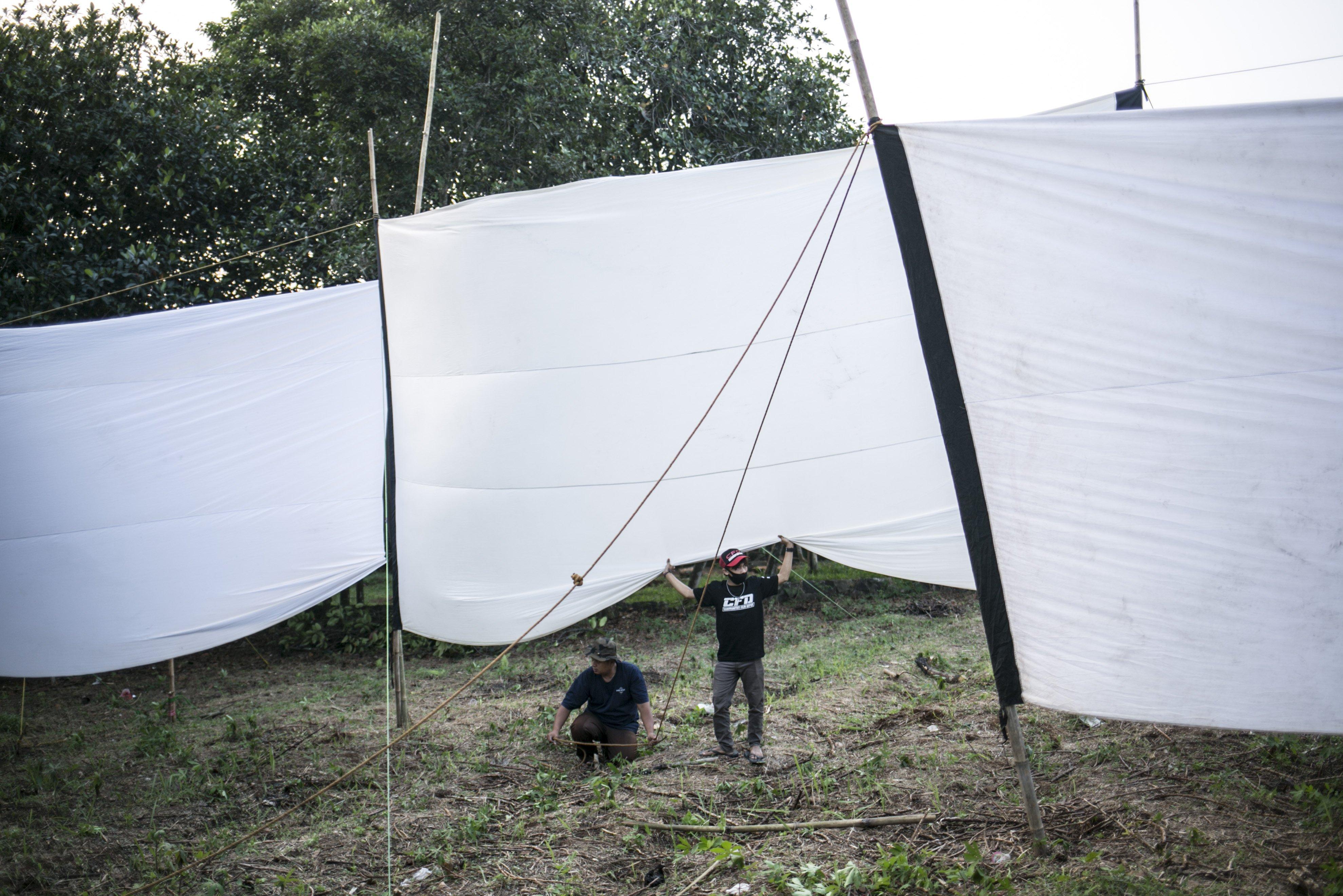 Teknisi menyiapkan layar putih untuk pemutaran film di Kawasan Sawangan, Depok, Jawa Barat, Sabtu (11/7/2020).