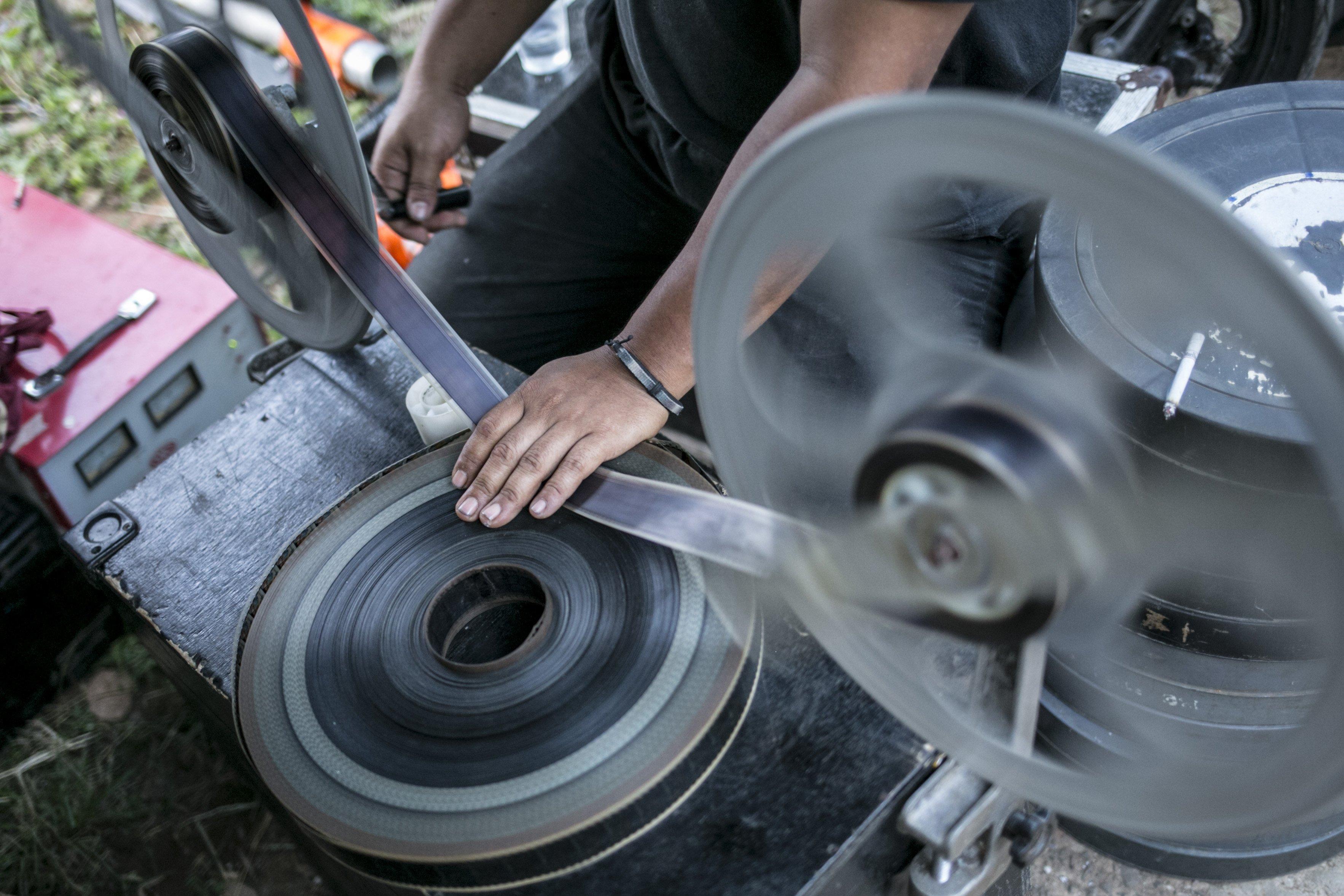 Teknisi mempersiapkan film 35mm untuk pemutaran layar tancap di Kawasan Sawangan, Depok, Jawa Barat, Sabtu (11/7/2020).
