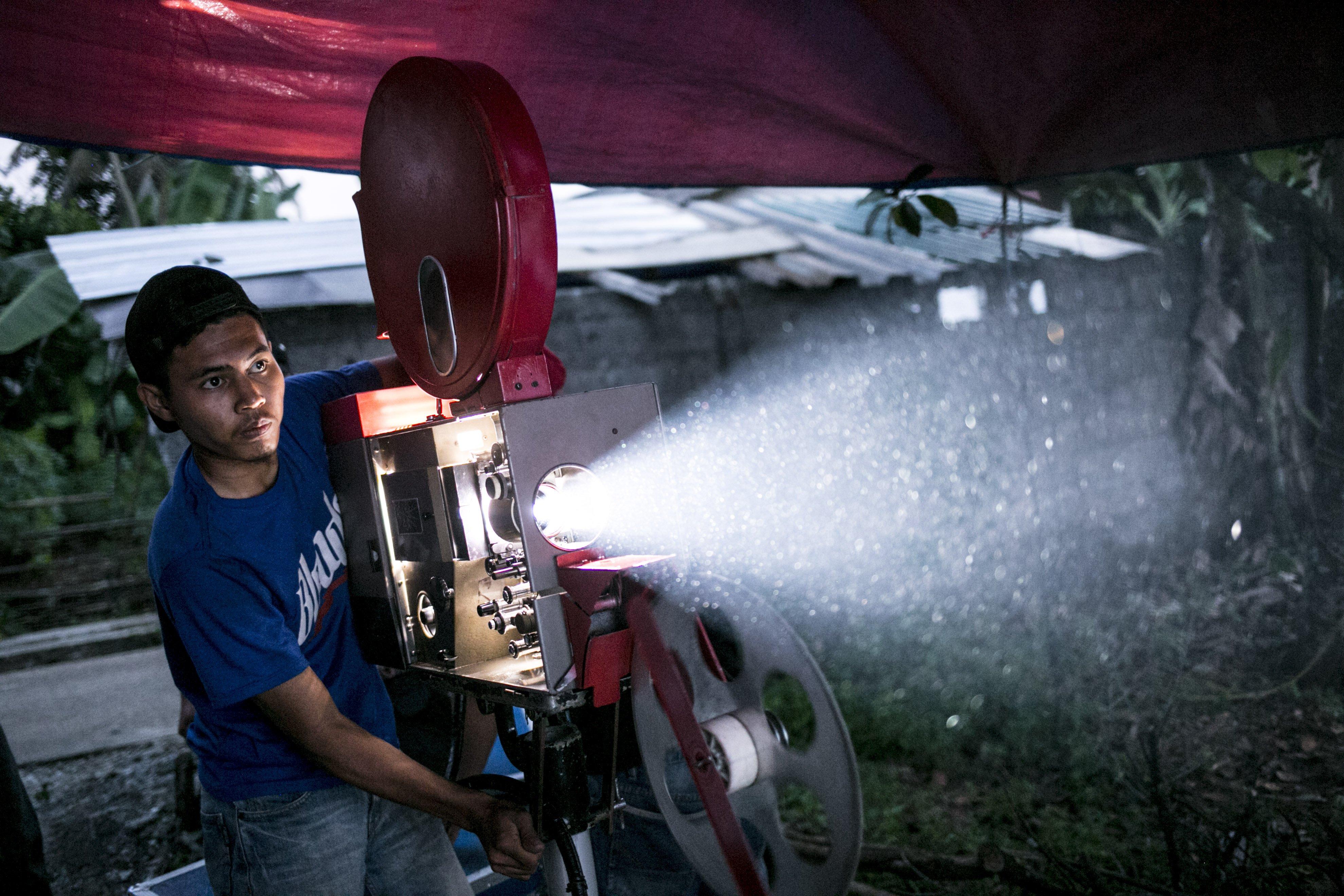 Teknisi mempersiapkan proyektor film 35mm untuk pemutaran layar tancap di Kawasan Sawangan, Depok, Jawa Barat, Sabtu (11/7/2020).