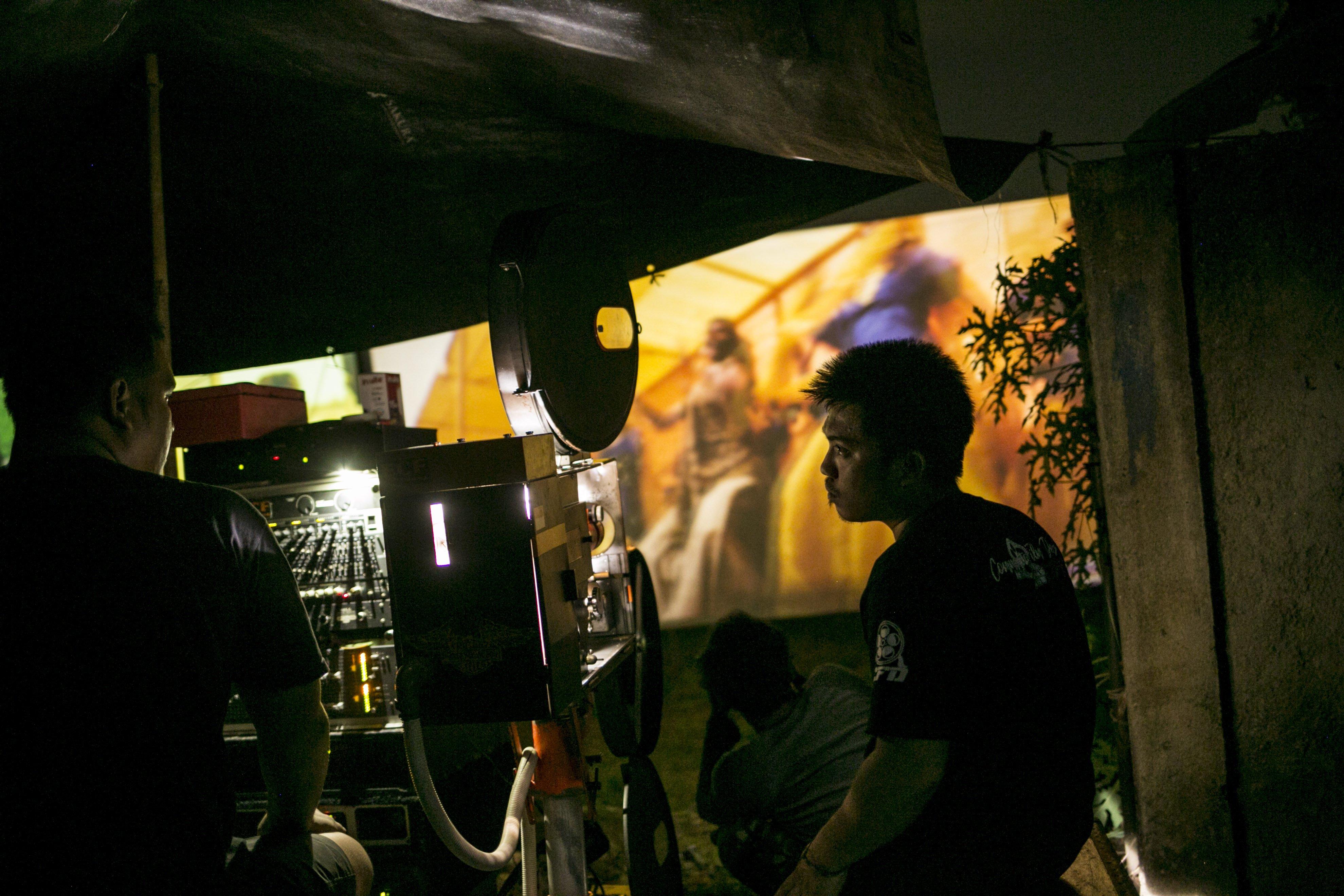 Teknisi memoperasikan proyektor film 35mm untuk pemutaran layar tancap di Kawasan Sawangan, Depok, Jawa Barat, Sabtu (11/7/2020).