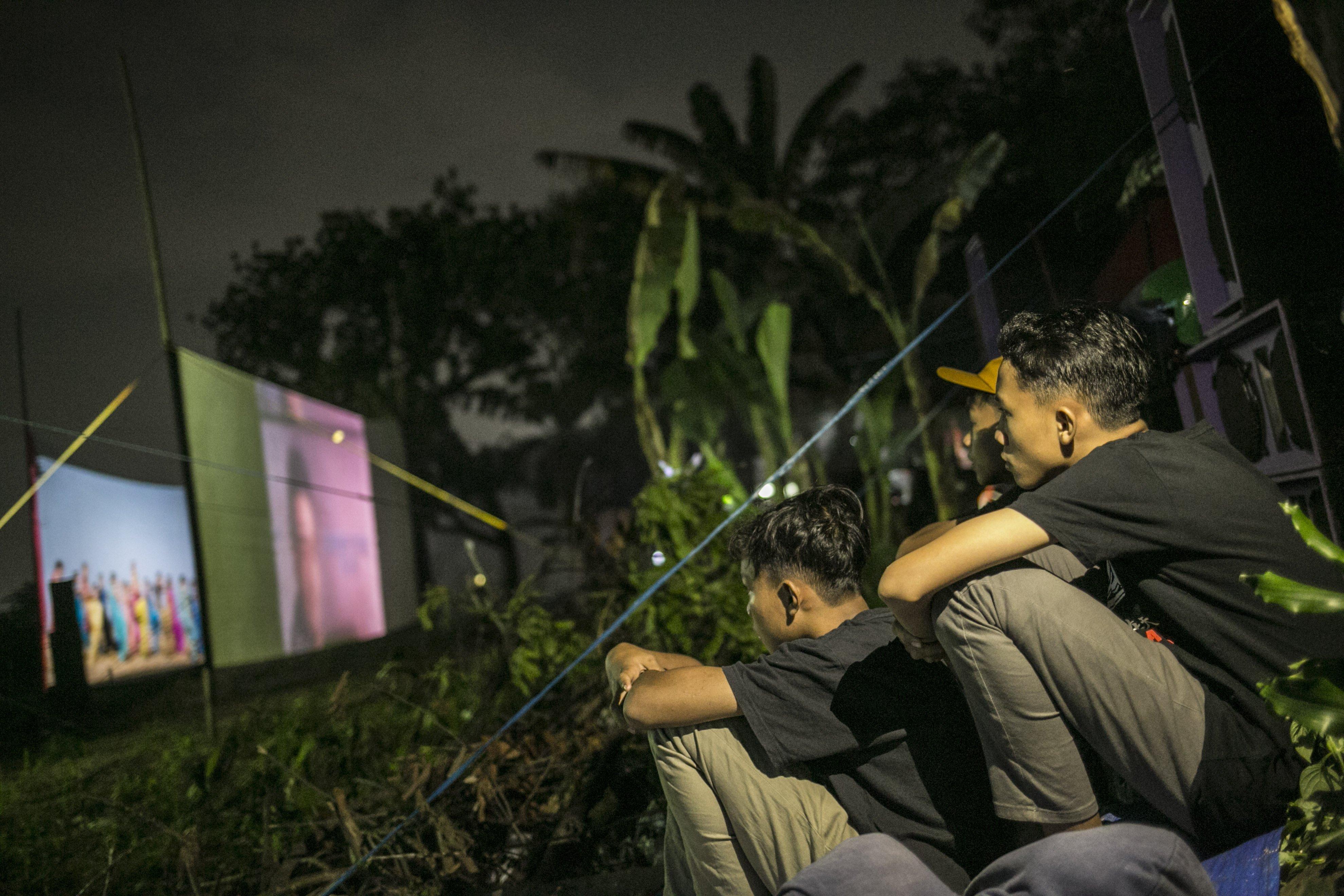 Warga menonron film layar tancap di Kawasan Sawangan, Depok, Jawa Barat, Sabtu (11/7/2020).
