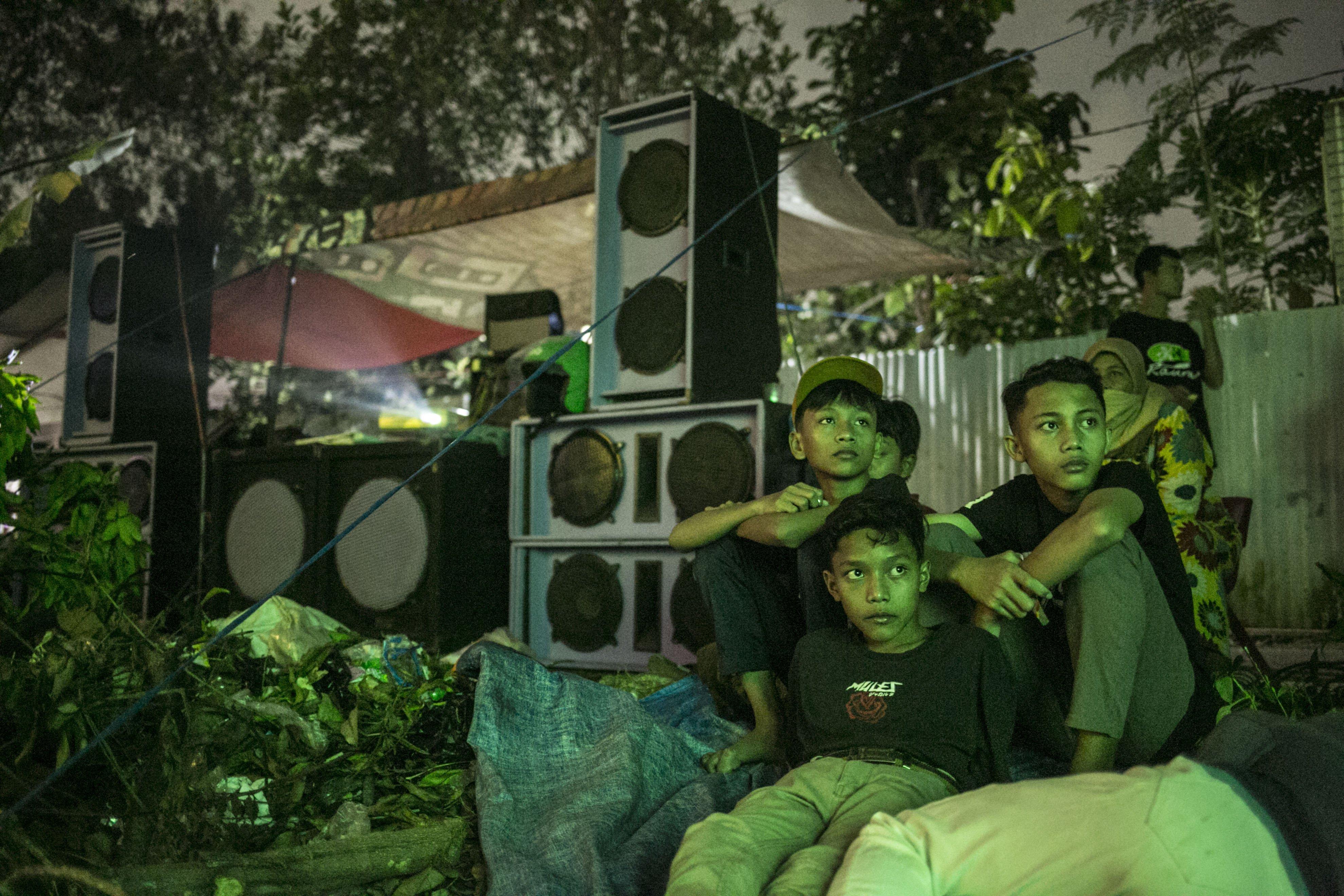 Warga menonton filim di layar tancap Kawasan Sawangan, Depok, Jawa Barat, Sabtu (11/7/2020).