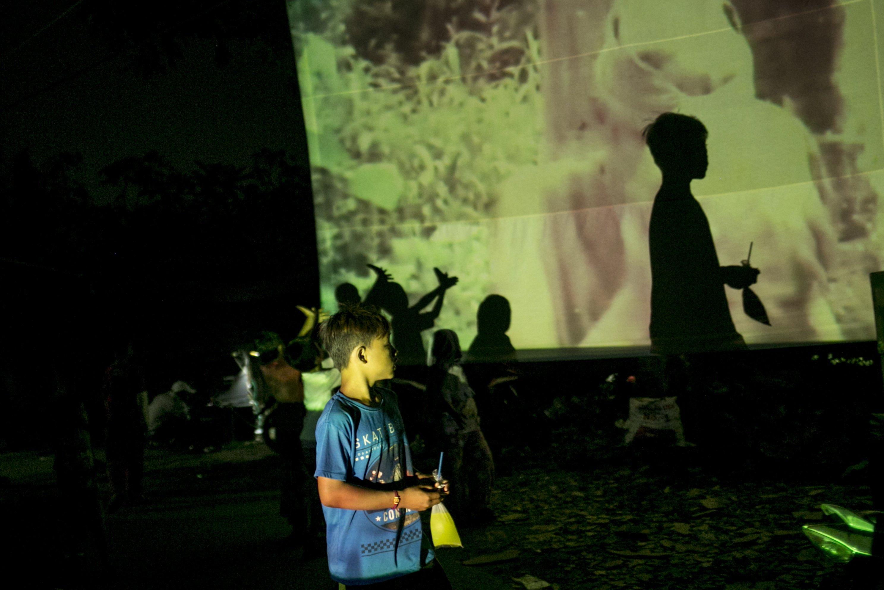 Sejumlah anak bermain dan menonton film di layar tancap Kawasan Sawangan, Depok, Jawa Barat, Sabtu (11/7/2020).