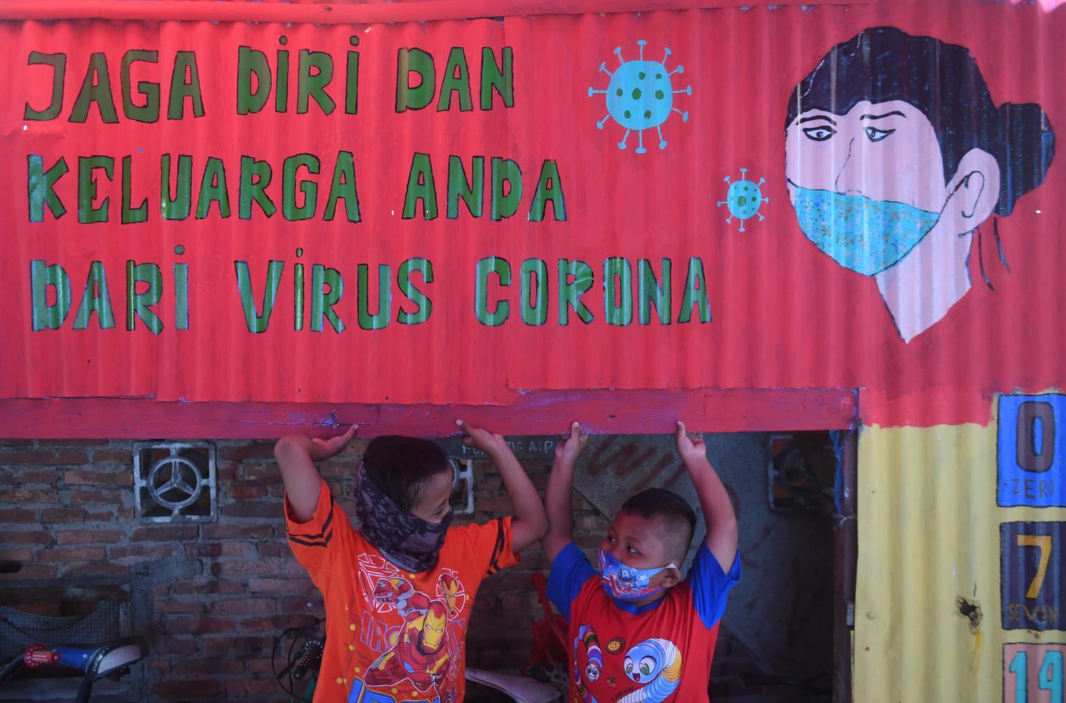 Seorang anak bermain di samping mural bertema COVID-19 di Jakarta, Senin (27/7/2020). Berdasarkan data dari Satgas Penanganan COVID-19 per 27 Juli 2020, kasus positif COVID-19 di Indonesia telah mencapai 100.303 kasus, dimana 58.173 orang dinyatakan sembuh dan 4.838 orang meninggal dunia.